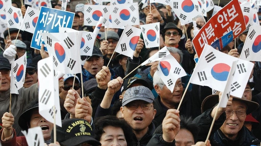 Protesters supporting South Korean President Park Geun-hye wave national flags during a rally opposing her resignation in Seoul, South Korea, Thursday, Nov. 17, 2016. South Korean prosecutors want to question Park this week over suspicion that she let a shadowy longtime confidante manipulate power from behind the scenes, an official said Sunday. (AP Photo/Ahn Young-joon)