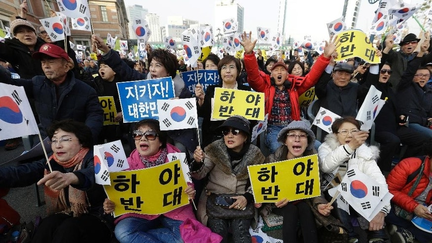 "Protesters supporting South Korean President Park Geun-hye shout slogans during a rally opposing the resignation of Park in Seoul, South Korea, Thursday, Nov. 17, 2016. South Korean prosecutors want to question Park this week over the suspicion that she let a shadowy, longtime confidante manipulate power from behind the scenes, an official said Sunday. The letters read ""Opposed Resignation"" (AP Photo/Ahn Young-joon)"