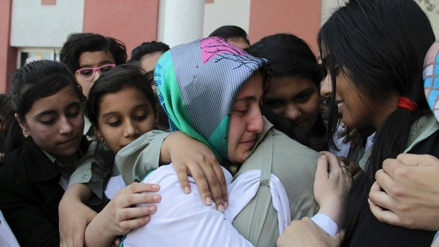 Pakistani students of the Pak-Turk International school comfort their Turkish teacher in Lahore, Pakistan, Thursday, Nov. 17, 2016. Pakistan's order for 400 Turkish nationals, mostly schoolteachers and their families, to leave the country within 72 hours was being challenged in court on Thursday as hundreds of students took to the streets to denounce the expulsions. (AP Photo/K.M. Chaudhry)