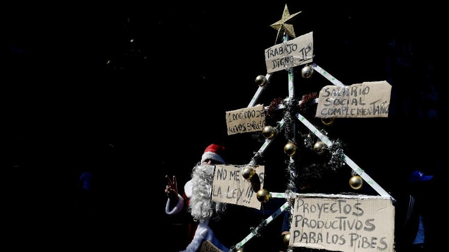 A demonstrator dressed as Santa Claus marches to the National Congress with a multi-pronged protest banner shaped as a Christmas tree during a protest demanding the approval of a stimulus bill to alleviate growing poverty, in Buenos Aires, Argentina, Friday, Nov. 18, 2016. Tens of thousands of Argentines flooded the capital streets, demanding the passage of the bill that would create a million jobs to face growing poverty levels. (AP Photo/Natacha Pisarenko)