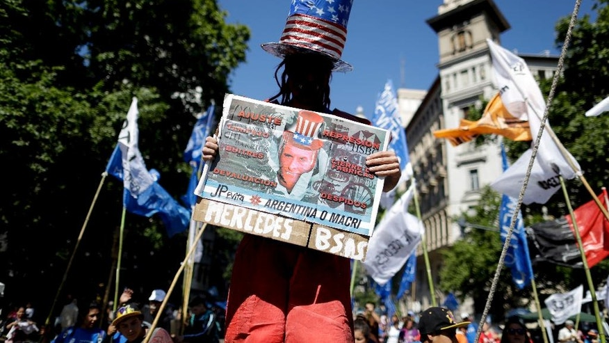 """A demonstrator marches to Congress with a banner reading in Spanish; """"Argentina or Macri"""" during a protest demanding the approval of a stimulus bill to alleviate growing poverty, in Buenos Aires, Argentina, Friday, Nov. 18, 2016. Tens of thousands of Argentines flooded the capital streets, demanding the passage of the bill that would create a million jobs to face growing poverty levels. (AP Photo/Natacha Pisarenko)"""