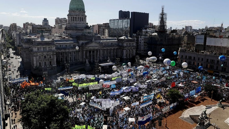Demonstrators stand before the Congress building demanding the approval of a stimulus bill to alleviate growing poverty, in Buenos Aires, Argentina, Friday, Nov. 18, 2016. Tens of thousands of Argentines flooded the capital streets, demanding the passage of the bill that would create a million jobs to face growing poverty levels. (AP Photo/Natacha Pisarenko)