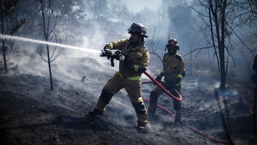 Firefighters work to put out a forest fire near the town of Placilla, Chile, Friday, Nov. 18, 2016. Authorities say that about 20 wildfires began last week amid a heat wave and are spreading quickly in the country's central region.  (AP Photo/Luis Hidalgo)