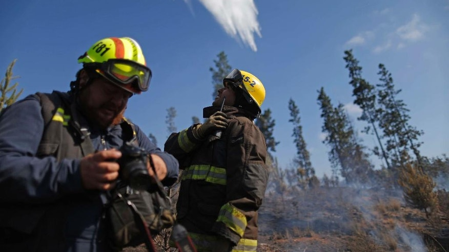 A firefighter looks up at a plane dropping water on a forest fire near in the town of Placilla, Chile, Friday, Nov. 18, 2016. Authorities say that about 20 wildfires began last week amid a heat wave and are spreading quickly in the country's central region. (AP Photo/Luis Hidalgo)