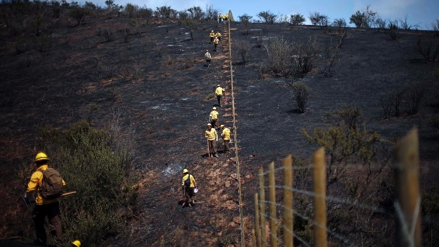 Firefighters climb a hill burned by a forest fire near the town of Villa Alemana, Chile, Friday, Nov. 18, 2016. Authorities say that about 20 wildfires began last week amid a heat wave and are spreading quickly in the country's central region.  (AP Photo/Luis Hidalgo)