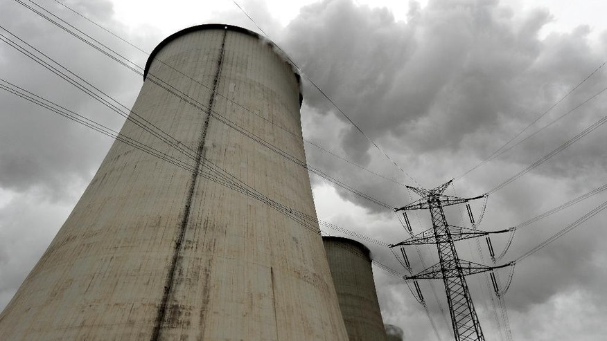 In this Friday, Oct. 28, 2016 photo an electricity pylon stands next to a cooling tower at the LEAG (Lusatian Energy Stock Company) lignite power plant in Jaenschwalde, eastern Germany. Scientists studying lifetime emissions of the world's current energy infrastructure say coal plants alone would blow the budget for 1.5 degrees C of warming, the lower threshold in the Paris climate agreement. (AP Photo/Michael Sohn)