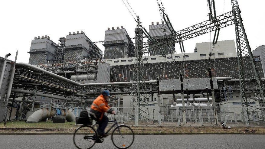 In this Friday, Oct. 28, 2016 photo an employee rides his bike past a turbine housing at the LEAG (Lusatian Energy Stock Company) lignite power plant in Jaenschwalde, eastern Germany. Scientists studying lifetime emissions of the world's current energy infrastructure say coal plants alone would blow the budget for 1.5 degrees C of warming, the lower threshold in the Paris climate agreement.  (AP Photo/Michael Sohn)