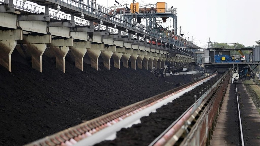 In this Friday, Oct. 28, 2016 photo raw lignite is transported on a conveyor at the LEAG (Lusatian Energy Stock Company) lignite power plant in Jaenschwalde, eastern Germany. Scientists studying lifetime emissions of the world's current energy infrastructure say coal plants alone would blow the budget for 1.5 degrees C of warming, the lower threshold in the Paris climate agreement. (AP Photo/Michael Sohn)