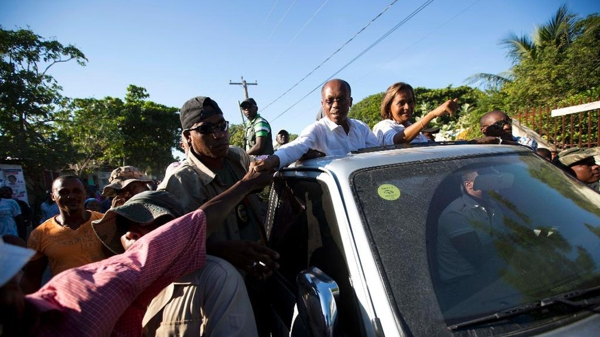 In this Wednesday, Nov. 16, 2016 photo, Haiti's former President Jean-Bertrand Aristide reaches out to shake a supporter's hand as he campaigns for presidential candidate Maryse Narcisse, riding alongside him in Arcahaie, Haiti. The electoral cycle began more than a year ago, but it's been repeatedly derailed. A first-round presidential vote held in October 2015 was annulled due to complaints of fraud.  ( AP Photo/Dieu Nalio Chery)