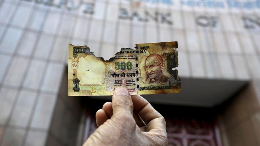 FILE - In this Nov. 16, 2016 file photo, a man holds a charred facsimile of the discontinued Indian currency 500 note after a protest by a traders association demanding adequate arrangement to exchange discontinued currency notes outside Reserve Bank of India in Kolkata, India. The sudden withdrawal of 86 percent of India's currency has left cash in short supply, retail sales stumbling and wholesale markets in turmoil. (AP Photo/Bikas Das, File)
