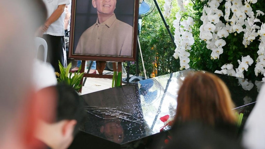 """A portrait of the late Philippine dictator Ferdinand Marcos is placed beside his granite tomb as hundreds of supporters attend a mass at his graveyard Saturday, Nov. 19, 2016, a day after Marcos was buried in a secrecy-shrouded ceremony at the Heroes' Cemetery in suburban Taguig city, east of Manila, Philippines. Long-dead Marcos was buried Friday at the country's Heroes' Cemetery in a secrecy-shrouded ceremony, a move approved by President Rodrigo Duterte that infuriated supporters of the """"people power"""" revolt that ousted Marcos three decades ago. (AP Photo/Bullit Marquez)"""