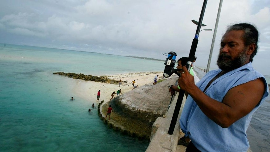 FILE - In this March 30, 2004, file photo, a man fishes on a bridge on Tarawa atoll, Kiribati. The island nation of Kiribati established a large shark sanctuary that will help ensure the creatures are protected across much of the central Pacific. Vice President Kourabi Nenem said at the sanctuary's launch on Friday, Nov. 18, 2016, that the nation was committed to protecting sharks from exploitation and overfishing. (AP Photo/Richard Voge, File)
