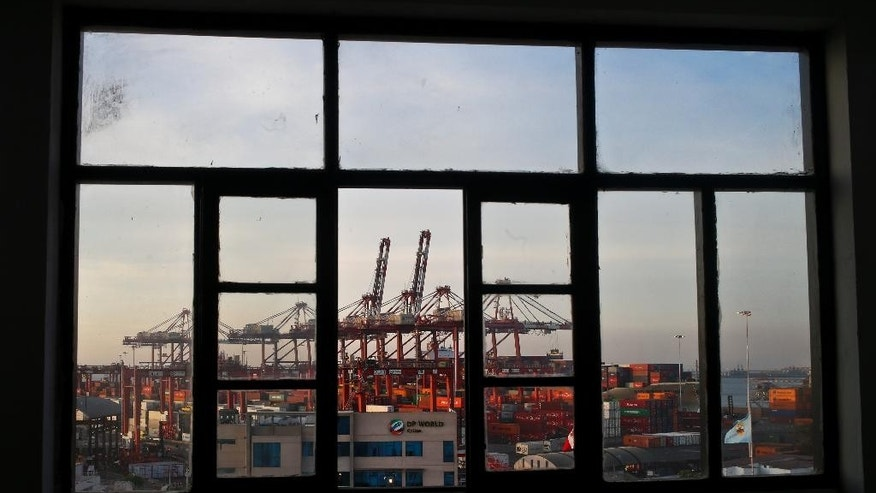Cranes of the port of El Callao, Peru, are seen through a window on Thursday, Nov. 17, 2016. Leaders of the Asia-Pacific Economic Cooperation will meet in Lima Nov. 19-20 to discuss the future of international trade policies, growth and improvement of life conditions for more than a third of the world's population. (AP Photo/Esteban Felix)