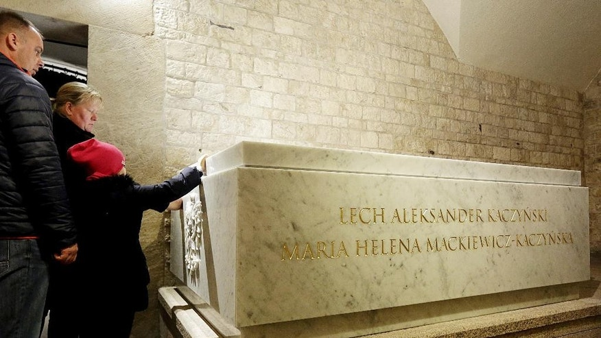 A family visiting the Wawel Cathedral looks at  the new white Carrara marble tomb just hours before the reburial of Poland's former President Lech Kaczynski and his wife in St. Leonard's Crypt at the Wawel cathedral in Krakow, Poland on Friday, Nov, 18, 2016. The presidential couple who died with 94 others in a plane crash in 2010 were exhumed Nov. 14, 2016 for forensic examination that is to determine the cause of their deaths and of the crash, amid theories circulated by the ruling party that the crash was an assassination attack. The presidential couple are to be laid to rest again in the new white marble tomb on Friday, in the presence of President Andrzej Duda and Prime Minister Beata Szydlo. (AP Photo/Jarek Praszkiewicz)