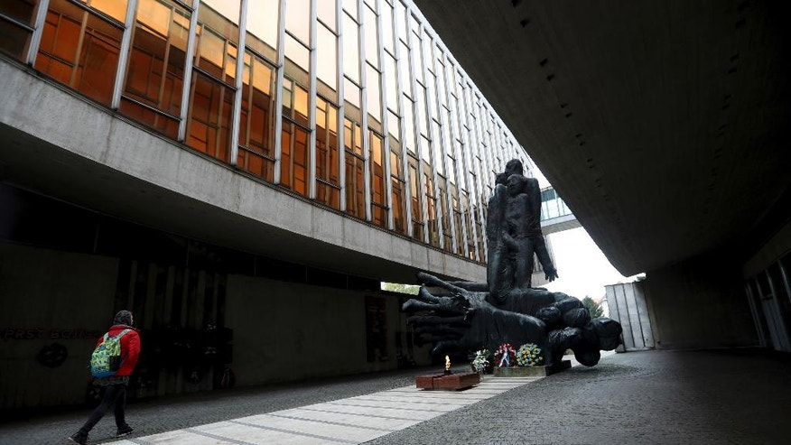 In this  Oct. 14, 2016 photo a  man walks past the Memorial of the Slovak National Uprising in Banska Bystrica, Slovakia. The wave of far-right parties across Europe has been gathering steam from Greece to France and Germany. While most of the continent's extreme forces have taken pains to steer clear of Nazi imagery, Slovakia's answer to the trend celebrates it. (AP Photo/Petr David Josek)