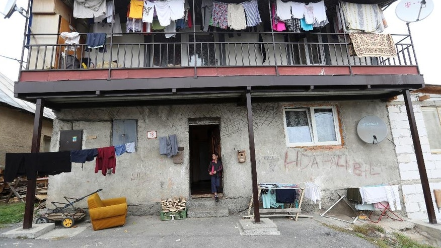 In this  Oct. 14, 2016 photo, a girl stands outside of a house in a poor Roma settlement near Banska Bystrica, Slovakia. The wave of far-right parties across Europe has been gathering steam from Greece to France and Germany. While most of the continent's extreme forces have taken pains to steer clear of Nazi imagery, Slovakia's answer to the trend celebrates it.(AP Photo/Petr David Josek)