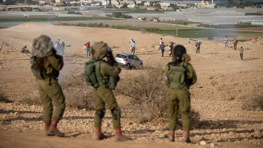 Palestinians and Israeli activists run away from a tear gas fired by Israeli soldiers during a demonstration against the construction of Jewish settlements in the Jordan Valley, in the West Bank, Thursday, Nov. 17, 2016. (AP Photo/Majdi Mohammed)