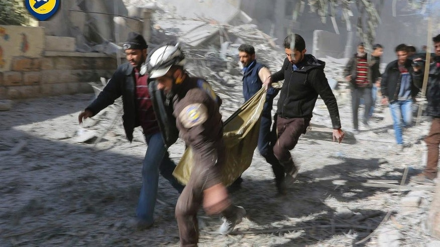 This photo provided by the Syrian Civil Defense White Helmets, which has been authenticated based on its contents and other AP reporting, shows Civil Defense workers and Syrian citizens carry a dead body in the neighborhood of Seif al-Dawleh in Aleppo, Syria, Saturday, Nov. 19, 2016. Government bombardment of besieged rebel-held neighborhoods in the northern city of Aleppo killed at least 20 people Saturday Syrian opposition activists said, a day after the health directorate said all hospital in opposition areas have been knocked out of service. (Syrian Civil Defense White Helmets via AP) سيف الدولة