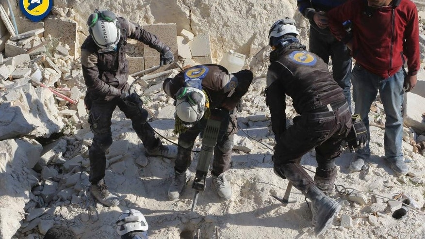 This photo provided by the Syrian Civil Defense White Helmets, which has been authenticated based on its contents and other AP reporting, shows Civil Defense workers using a drill to dig through rubble in search for victims in Aleppo, Syria, Saturday, Nov. 19, 2016. Government bombardment of besieged rebel-held neighborhoods in the northern city of Aleppo killed at least 20 people Saturday Syrian opposition activists said, a day after the health directorate said all hospital in opposition areas have been knocked out of service. (Syrian Civil Defense White Helmets via AP)