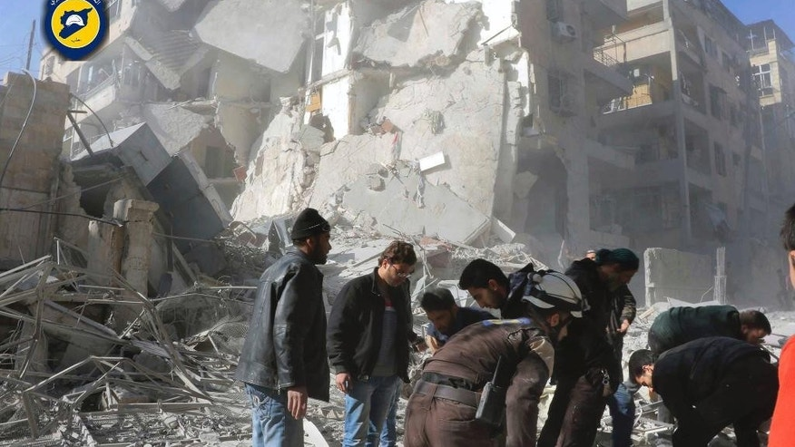 This photo provided by the Syrian Civil Defense White Helmets, which has been authenticated based on its contents and other AP reporting, shows Civil Defense workers and Syrian citizens inspect damage buildings after airstrikes hit the Seif al-Dawleh neighborhood in Aleppo, Syria, Saturday, Nov. 19, 2016. Government bombardment of besieged rebel-held neighborhoods in the northern city of Aleppo killed at least 20 people Saturday Syrian opposition activists said, a day after the health directorate said all hospital in opposition areas have been knocked out of service. (Syrian Civil Defense White Helmets via AP)