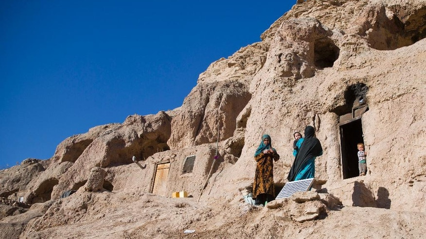 In this Monday, Nov. 7, 2016 photo, Marzia, 30, in blue, talks to her neighbor near her cave in Bamiyan, Afghanistan. Marzia and her husband Qadeer thought themselves lucky when they moved into a 1,700-year-old Buddhist cave hand-carved into the side of a mountain in Afghanistan's central highlands _ it was clean and dry, warm in the winter, cool in the summer, and there was plenty of work on the local farms. (AP Photos/Massoud Hossaini)