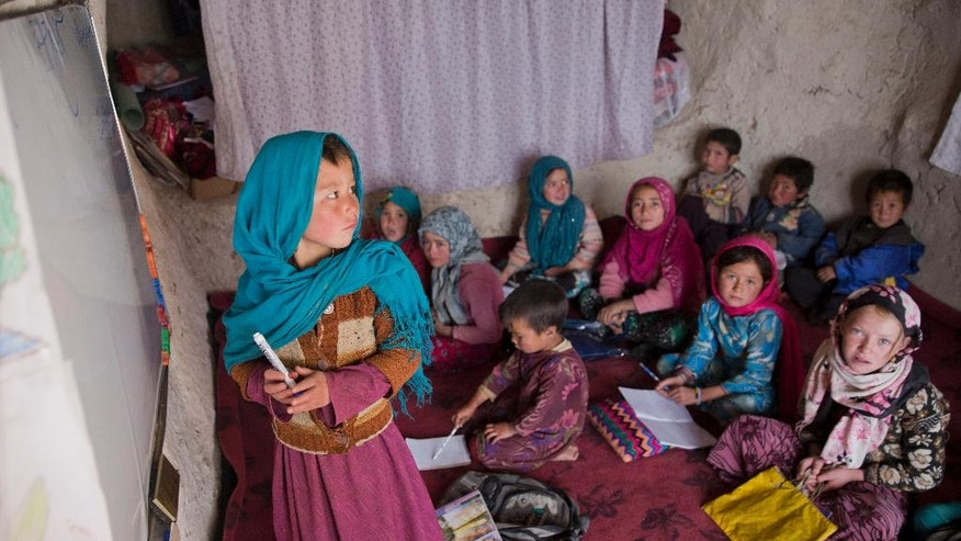 In this Monday, Nov. 7, 2016 photo, Afghan schoolgirls and boys listen to their teacher in their cave classroom, in Bamiyan, Afghanistan. The cave-dwelling families of Afghanistan's Bamiyan province struggle to get by on the bare minimum. But even this bare-bones way of life is now under threat as the government relocates residents to pave the way for transforming the man-made grottoes into a global tourist destination.(AP Photos/Massoud Hossaini)