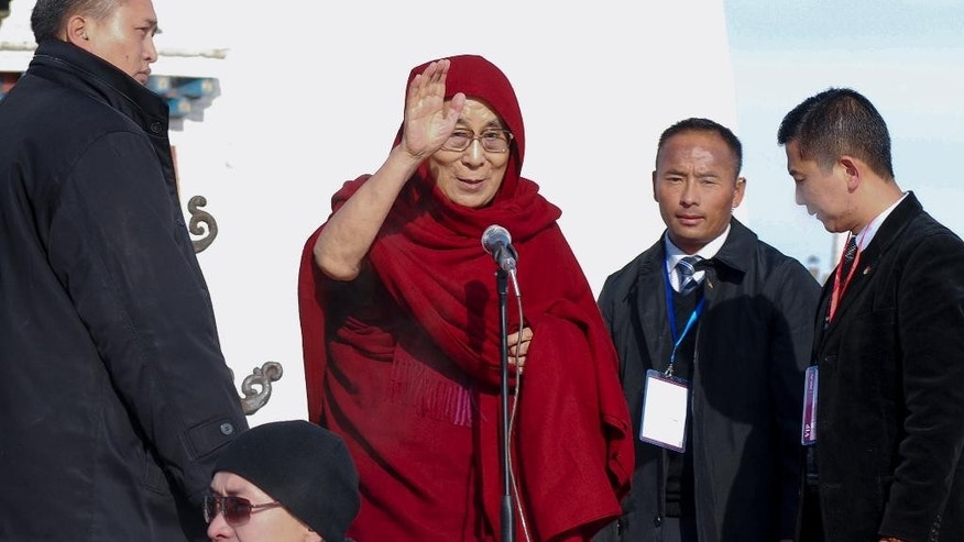 Dalai Lama, center, waves as he arrives at the Janraiseg temple of Gandantegchinlen monastery to greet Mongolian people in Ulaanbaatar, Mongolia, Saturday, Nov. 19, 2016. Dalai Lama has preached to thousands of supporters Saturday in Mongolia on a visit set to test the country's ties with its powerful neighbor, China. (AP Photo/ Ganbat Namjilsangarav)