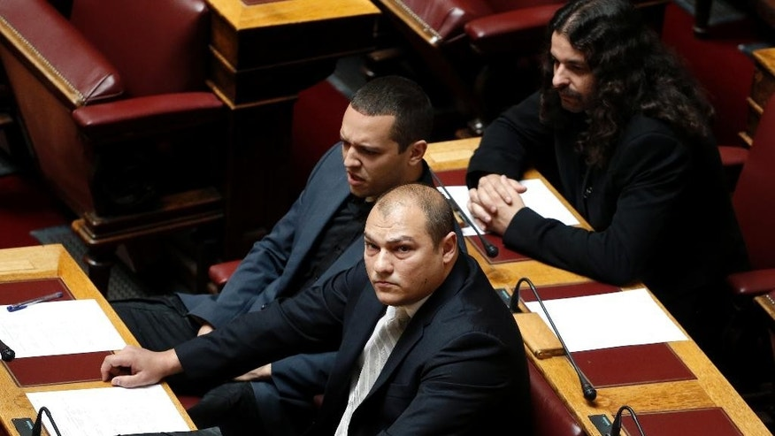 FILE - In this photo taken May 7, 2014, the extreme right Golden Dawn party lawmaker Georgios Germenis, front, sits with Costas Barbarousis, top right, and Ilias Kasidiaris, both Golden Dawn members of the parliament, during a parliament session in Athens. Greek police say Germenis has been briefly hospitalized after being set upon by a group of people, possibly anarchists, who hit him with an iron bar and sprayed him with pepper spray on Saturday Nov. 19, 2016. (AP Photo/ Petros Giannakouris, File)