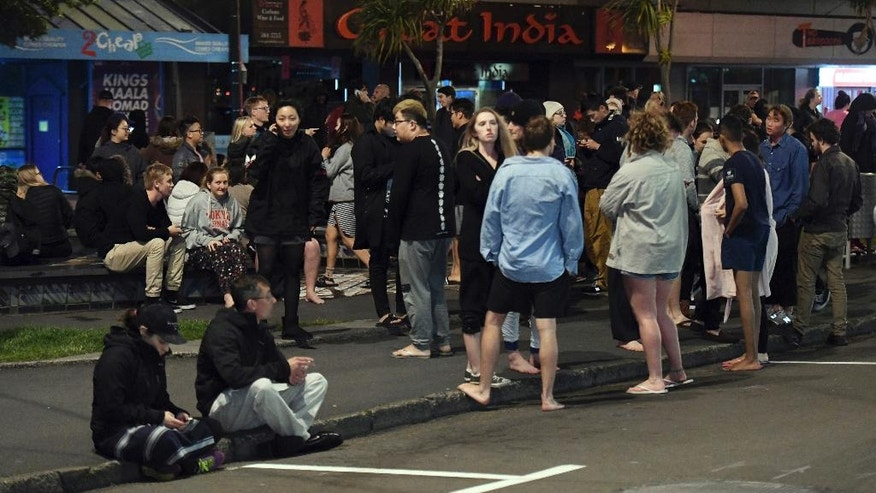 FILE - In this Monday, Nov. 14, 2016 file photo, people evacuated from buildings along Dixon Street crowd on the street in Wellington after a powerful earthquake hit New Zealand. The huge earthquake that hit New Zealand this past week, buckling roads, uplifting sections of coastline and killing two people, also exposed problems in how the country monitors its earthquake risk and prepares for tsunamis. And it raised questions about whether the city of Wellington put people at risk by reopening buildings too soon. (Ross Setford/SNPA via AP, File)
