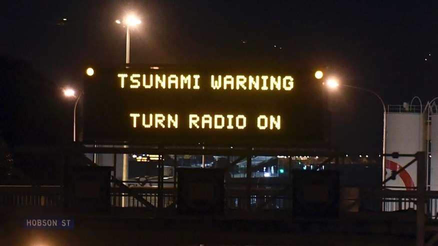 FILE - In this Monday, Nov. 14, 2016 file photo, a tsunami warning is displayed on a motorway in Wellington after a major earthquake struck New Zealand. The huge earthquake that hit New Zealand this past week, buckling roads, uplifting sections of coastline and killing two people, also exposed problems in how the country monitors its earthquake risk and prepares for tsunamis. And it raised questions about whether the city of Wellington put people at risk by reopening buildings too soon. (Ross Setford/SNPA via AP, File)