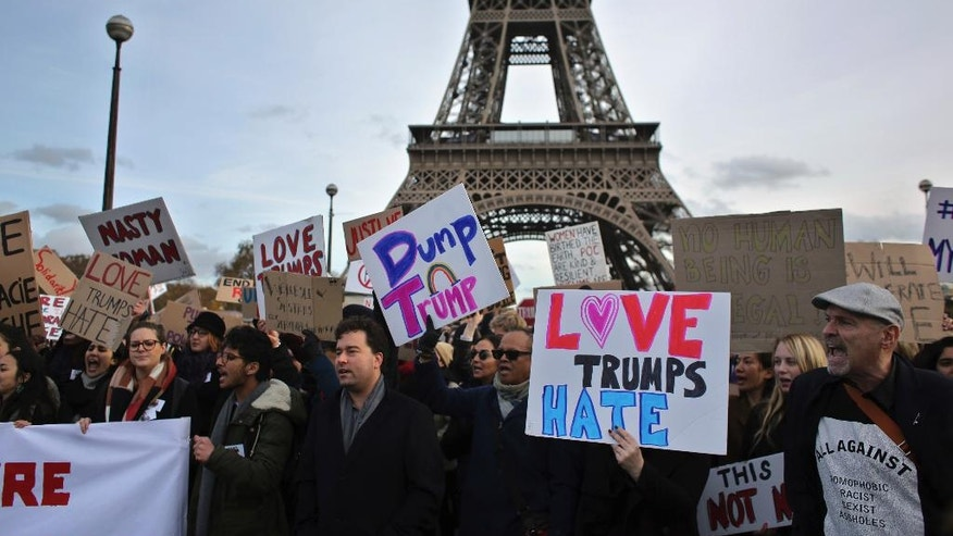 People hold banners and shout slogans against US President-elect Donald Trump, in Paris, Saturday, Nov. 19, 2016. A few hundreds of critics of Trump have marched through Paris to express concern about his respect for human rights, women and minorities. (AP Photo/Thibault Camus)