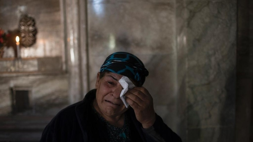 A woman wipes her tears during a ceremony in the Saint George church in Bashiqa, east of Mosul, Iraq, Saturday, Nov. 19, 2016. In heavily damaged Bashiqa, Christians rang the bells of Saint George's church for the first time to celebrate its liberation from Islamic State, which was driven from the city earlier this month. (AP Photo/Felipe Dana)