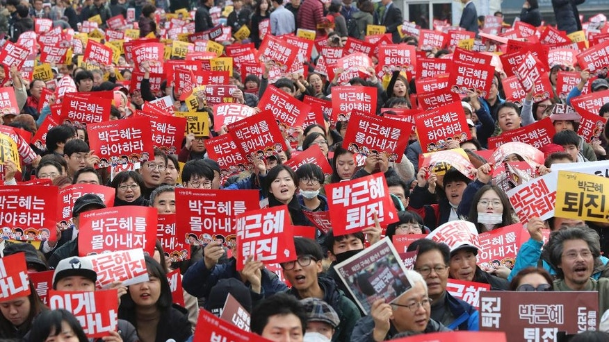 "South Korean protesters hold up cards during a rally calling for South Korean President Park Geun-hye to step down in Seoul, South Korea, Saturday, Nov. 19, 2016. For the fourth straight weekend, masses of South Koreans were expected to descend on major avenues in downtown Seoul demanding an end to the presidency of Park, who prosecutors plan to question soon over an explosive political scandal. The letters read ""Park Geun-hye should step down."" (AP Photo/Lee Jin-man)"