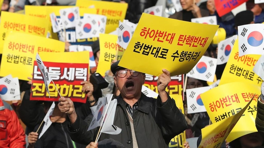 "Protesters supporting South Korean President Park Geun-hye shout slogans during a rally opposing her resignation in Seoul, South Korea, Saturday, Nov. 19, 2016. For the fourth straight weekend, masses of South Koreans were expected to descend on major avenues in downtown Seoul demanding an end to the presidency of Park Geun-hye, who prosecutors plan to question soon over an explosive political scandal. The letters read ""Opposed Resignation."" (AP Photo/Lee Jin-man)"