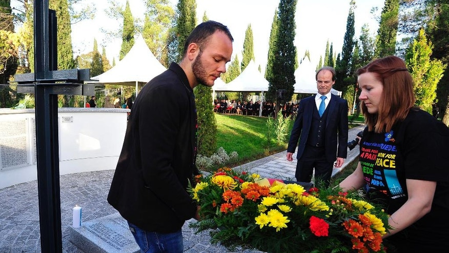 German ambassador in Montenegro Hans Gunther Mattern, center, lays flowers at the monument during a funeral service of the mortal remains of German soldiers who died during World War II at the war cemetery, in the village of Golubovci, about 10 kilometers (6 miles) south of the Montenegro capital Podgorica, Sunday, Nov. 19, 2016. Officials have inaugurated a cemetery for hundreds of German soldiers killed in Montenegro during World War II hailing it as an act of reconciliation that is important for the future. (AP Photo/Risto Bozovic)