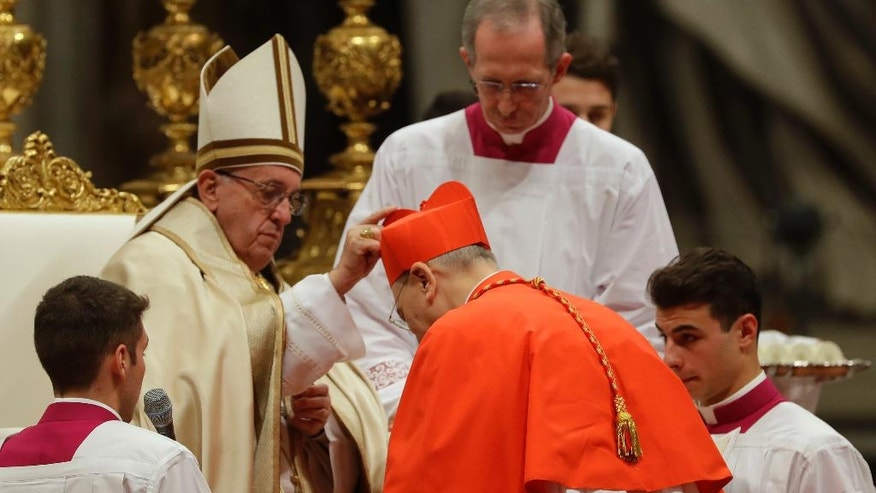 New Cardinal Mario Zenari, Apostolic Nuncio in Syria, receives the red three-cornered biretta hat during a consistory inside the St. Peter's Basilica at the Vatican, Saturday, Nov. 19, 2016. In the ceremony to formally give the Catholic church 17 new cardinals, Francis lamented how immigrants, refugees, and those from different races or faiths are increasingly seen as enemies. (AP Photo/Gregorio Borgia)