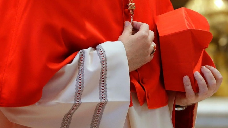 A cardinal holds a red three-cornered biretta hat before a consistory inside the St. Peter's Basilica at the Vatican, Saturday, Nov. 19, 2016. Pope Francis has named 17 new cardinals, 13 of them under age 80 and thus eligible to vote in a conclave to elect his successor. (AP Photo/Gregorio Borgia)
