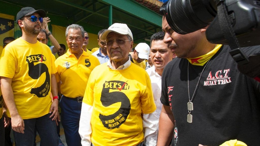 From Left to right; former Chief Minister of Kedah Mukhriz Mahathir, former Deputy Prime Minister of Malaysia Muhyiddin Yassin, and former Malaysia Prime Minister Mahathir Mohamad, walk during a rally in Kuala Lumpur, Malaysia, on Saturday, Nov. 19, 2016. Tens of thousands of Malaysians wearing yellow T-shirts and blowing horns defiantly held a major rally in the capital Saturday to demand the resignation of embattled Prime Minister Najib Razak. (AP Photo/Lim Huey Teng)