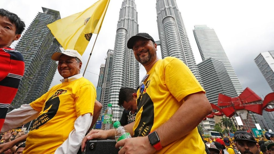 Malaysia's former Prime Minister Mahathir Mohamad, left, arrives at a rally by the Coalition for Clean and Fair Elections (Bersih), in Kuala Lumpur, Malaysia, Saturday, Nov. 19, 2016. Tens of thousands of Malaysians wearing yellow T-shirts and blowing horns defiantly held a major rally in the capital Saturday to demand the resignation of embattled Prime Minister Najib Razak. (AP Photo/Vincent Thian)