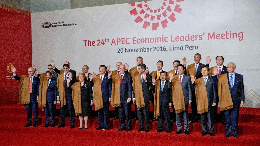 Leaders of Asia Pacific Economic Cooperation, APEC, front row from left, Australia's Prime Minister Malcolm Turnbull, Brunei's Sultan Hassanal Bolkiah, Canada's Prime Minister Justin Trudeau, Chile's President Michelle Bachelet, China's President Xi Jinping, Peru's President Pedro Kuczynski, Hong Kong's Chief Executive Leung Chun-ying, Indonesia's Vice President Jusuf Kalla, Japan's Prime Minister Shinzo Abe, South Korea's Prime Minister Hwang Kyo-ahn and Malaysia's Prime Minister Najib Razak, and back row from left, Mexico's Secretary of Economy Ildefonso Guajardo, New Zealand's Prime Minister John Key, Papua New Guinea's Prime Minister Peter O'Neill, Philippines's Secretary of Department of Foreign Affairs Perfecto Yasay, Russia's President Vladimir Putin, Singapore's Prime Minister Lee Hsien Loong, Taiwan 's special APEC envoy James Soong, Thailand's Deputy Prime Minister Prajin Juntong, US President Barack Obama and Vietnam's President Tran Dai Quang, wave during the group photo in Lima, Peru, Sunday, Nov. 20, 2016. (AP Photo/Pablo Martinez Monsivais)