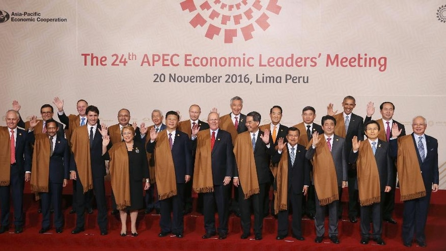 Leaders of Asia Pacific Economic Cooperation, APEC, wave during the group photo in Lima, Peru, Sunday, Nov. 20, 2016. Front row, from left: Australia's Prime Minister Malcolm Turnbull, Brunei's Sultan Hassanal Bolkiah, Canada's Prime Minister Justin Trudeau, Chile's President Michelle Bachelet, China's President Xi Jinping, Peru's President Pedro Kuczynski, Hong Kong's Chief Executive Leung Chun-ying, Indonesia's Vice President Jusuf Kalla, Japan's Prime Minister Shinzo Abe, South Korea's Prime Minister Hwang Kyo-ahn and Malaysia's Prime Minister Najib Razak. Back row, from left: Mexico's Secretary of Economy Ildefonso Guajardo, New Zealand's Prime Minister John Key, Papua New Guinea's Prime Minister Peter O'Neill, Philippines's Secretary of Department of Foreign Affairs Perfecto Yasay, Russia's President Vladimir Putin, Singapore's Prime Minister Lee Hsien Loong, Taiwan 's special APEC envoy James Soong, Thailand's Deputy Prime Minister Prajin Juntong, US President Barack Obama and Vietnam's President Tran Dai Quang. (AP Photo/Martin Mejia)