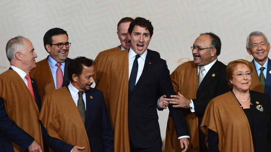 Canadian Prime Minister Justin Trudeau jokes around with fellow APEC leaders as they take part in the official family photo at the APEC Summit in Lima, Peru, Sunday, Nov. 20, 2016. (Sean Kilpatrick /The Canadian Press via AP)