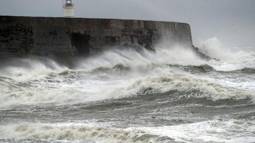 Waves crash into the wall at Newhaven in south England, as a storm, Storm Angus, the year's first big winter storm in Britain, lashes England's south coast, Sunday Nov. 20, 2016. Forecasters say winds of 68 mph (110 kph) hit the south coast early Sunday, with a gust of 97 mph (156 kph) recorded offshore. (Andrew Matthews/PA via AP)
