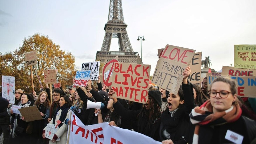 People hold banners and shout slogans against President-elect Donald Trump, in Paris, Saturday, Nov. 19, 2016. A few hundreds of critics of U.S. president-elect Donald Trump have marched through Paris to express concern about his respect for human rights, women and minorities. (AP Photo/Thibault Camus)
