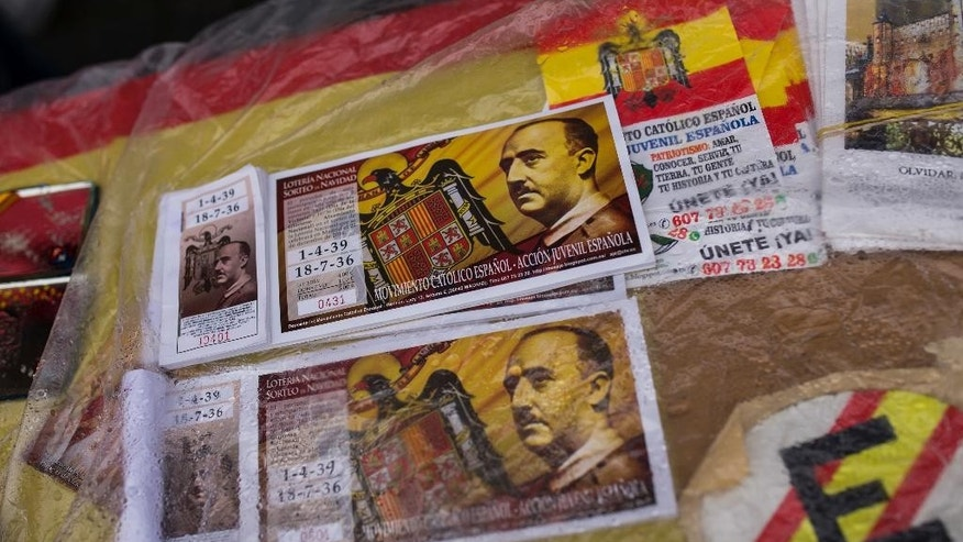 Lottery tickets with the face of former Spanish dictator Francisco Franco are displayed to be sold during a rally commemorating Franco's death in Madrid, Sunday, Nov. 20, 2016. Hundreds of Spaniards nostalgic for the nation's fascist dictatorship gathered in a Madrid square on Sunday to commemorate the 41st anniversary of Francisco Franco's death. (AP Photo/Francisco Seco)