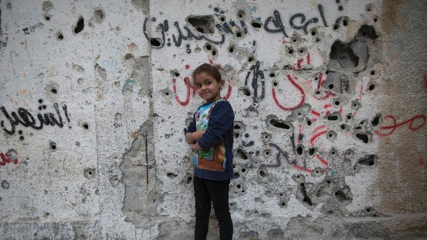 In this photo taken Thursday, Nov. 10, 2016, a Palestinian girl poses in front of a wall riddled with bullet marks from the latest Palestinian police offensive in Balata refugee camp, in the West Bank. Fierce shootouts between Palestinian police and gunmen in the West Bank point to worsening rivalries within the long-ruling Fatah faction, where critics see the leadership as corrupt and out of touch. Behind the tensions are a combustible power struggle between President Mahmoud Abbas, and exiled rival Mohammed Dahlan. (AP Photo/Nasser Nasser)