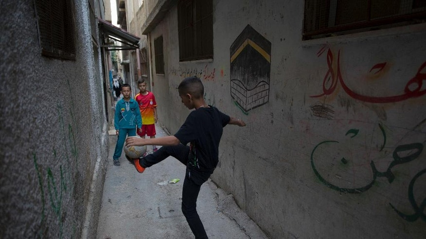 In this photo taken Thursday, Nov. 10, 2016, Palestinian refugee boys play football in an alley in Balata refugee camp, in the West Bank. Fierce shootouts between Palestinian police and gunmen in the West Bank point to worsening rivalries within the long-ruling Fatah faction, where critics see the leadership as corrupt and out of touch. Behind the tensions are a combustible power struggle between President Mahmoud Abbas, and exiled rival Mohammed Dahlan. (AP Photo/Nasser Nasser)
