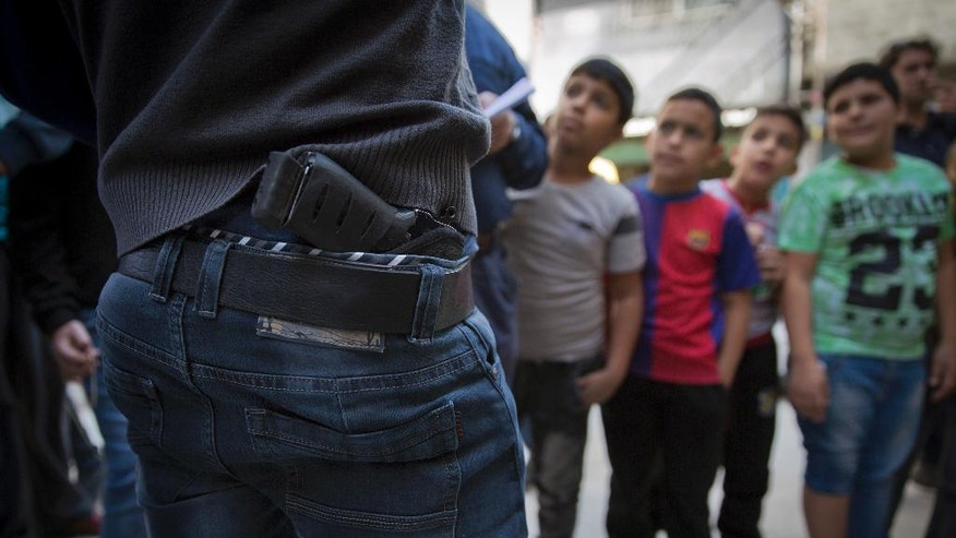 In this photo taken Thursday, Nov. 10, 2016, Palestinian refugee boys gather by armed men who are wanted by the Palestinian Authority security, one with a concealed weapon, while talking to the Associated Press, in Balata refugee camp, in the West Bank. Fierce shootouts between Palestinian police and gunmen in the West Bank point to worsening rivalries within the long-ruling Fatah faction, where critics see the leadership as corrupt and out of touch. Behind the tensions are a combustible power struggle between President Mahmoud Abbas, and exiled rival Mohammed Dahlan. (AP Photo/Nasser Nasser)