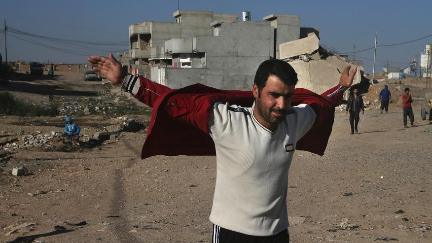 An Iraqi man opens his jacket and and raises his hands to show the army that he's not wearing an explosive belt, as he arrives to receive food supplies, at al-Arbajiyeh neighborhood, in Mosul, Iraq, Saturday, Nov. 19, 2016. Iraqi troops faced stiff resistance Saturday from Islamic State militants as they pushed deeper into eastern Mosul, backed by aerial support from the U.S.-led international coalition, a senior military commander said. (AP Photo/Hussein Malla)