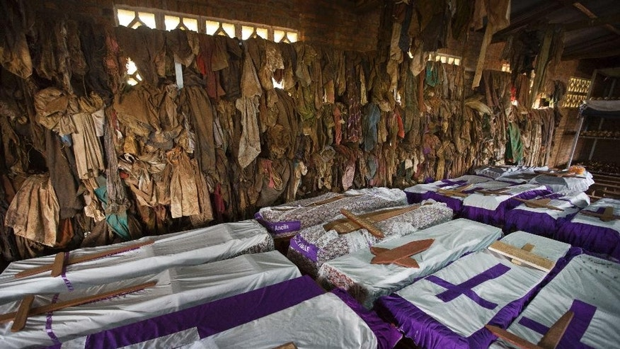 FILE - In this Friday, April 4, 2014 file photo, the clothes of some of those who were slaughtered as they sought refuge inside the church hang above coffins containing the remains of multiple victims, as a memorial to the thousands who were killed in and around the Catholic church during the 1994 genocide in Ntarama, Rwanda. The Catholic Church in Rwanda apologized on Sunday, Nov. 20, 2016, for the church's role in the 1994 genocide, saying it regretted the actions of those who participated in the massacres. (AP Photo/Ben Curtis, File)